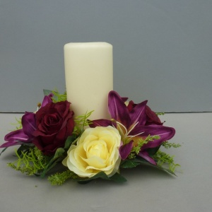 Candle ring with artificial burgundy roses and lilies